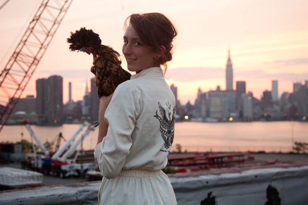 Annie Novak holding a chicken on her rooftop farm in Greenpoint, Brooklyn.